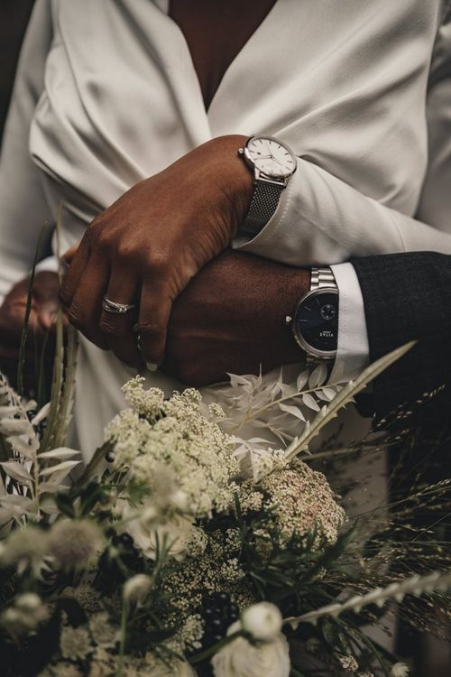 Bride and groom embracing showing off their Vitae watches