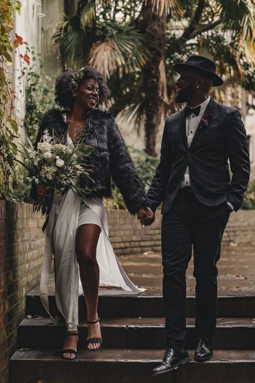 Bride in satin dress and faux fur coat holding hands with her groom