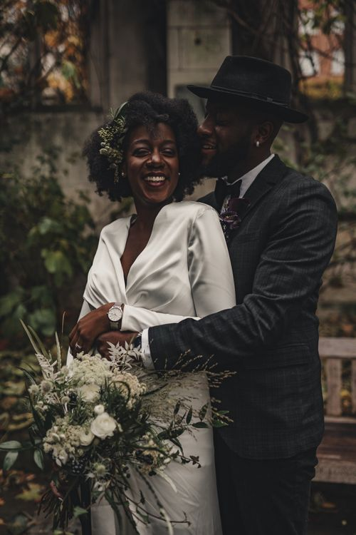 Groom in bow tie and hat embracing his bride with wrap satin dress