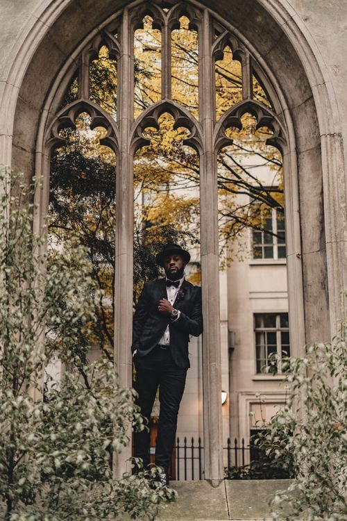 Stylish groom in bow tie and hat standing at St Dunstan in the East  church gardens