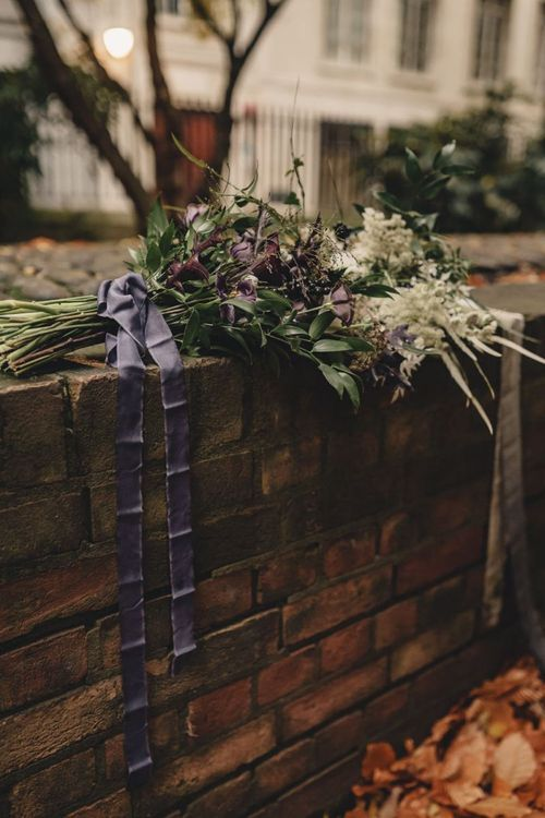White and purple wedding bouquets with foliage tied with ribbon