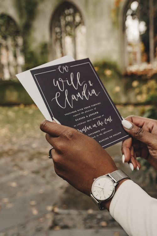Bride holding a black and white wedding invitation  with white nail polish