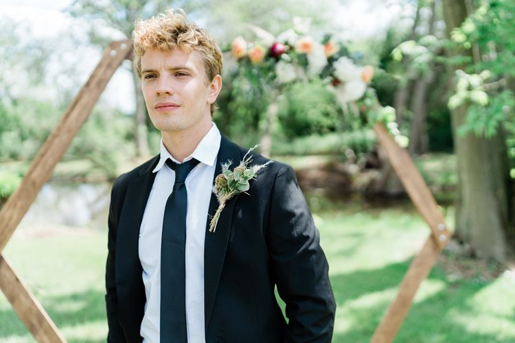 Stylish Groom in Black suit and Tie with Foliage and Pampas Grass Buttonhole  Standing in Front of a Hexagonal Altar