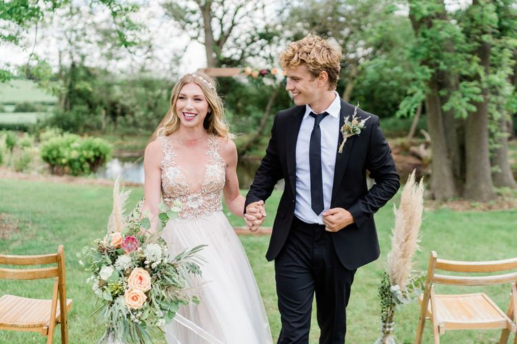 Bride in Watters wedding Dress and Hair Vine Holding Hands with Groom in Black Suit and Tie