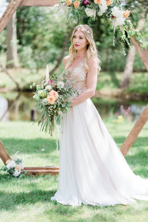 Beautiful Bride in Watters Wedding Dress Holding a Foliage and Peach Rose Wedding Bouquet