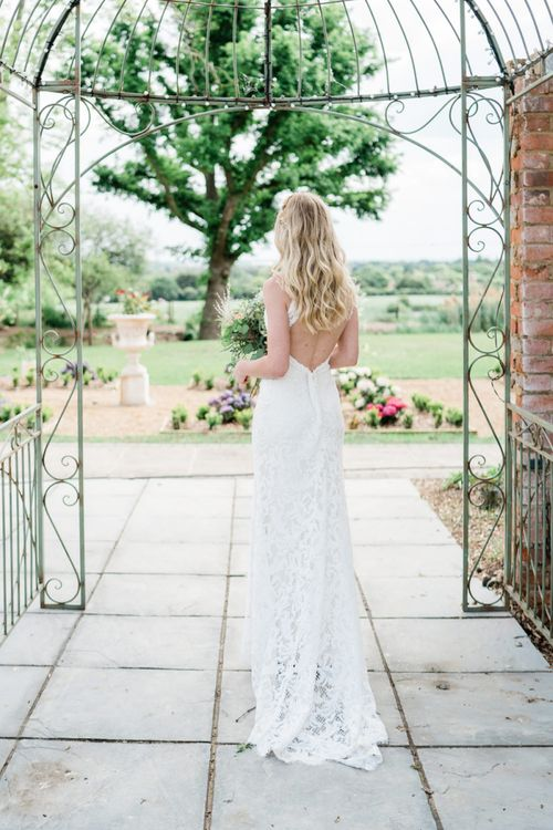 Bride in Low Back Lace Watters Wedding Dress with Long Wavy Hair
