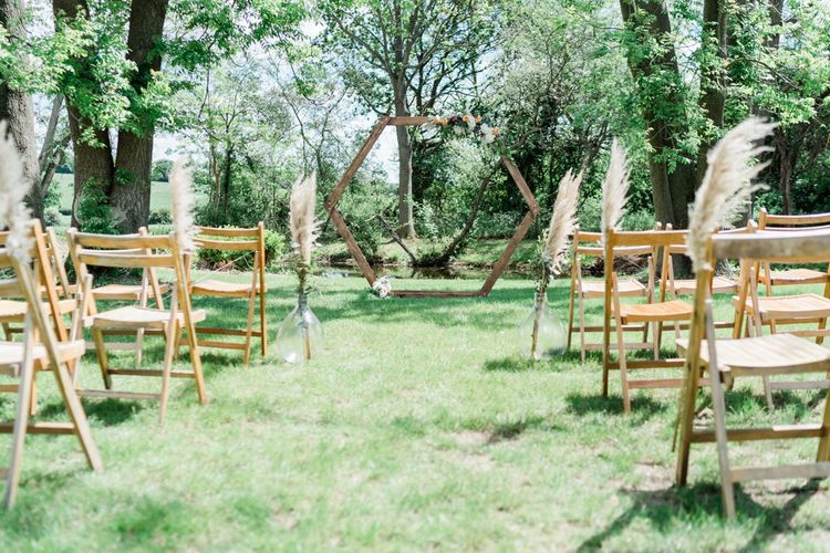 Outdoor Wedding Ceremony Set up with Wooden Chairs Decorated with Pampas Grass and Hexagonal Altar