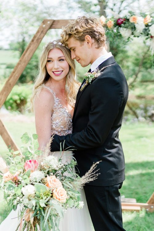 Smiling Bride in Watters Wedding Dress and Groom in Black Suit Standing at the Hexagonal Altar