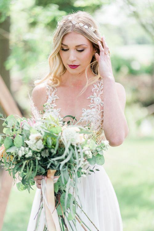 Bride in Watters Wedding Dress and Hair Vine Holding a Wild Wedding Bouquet