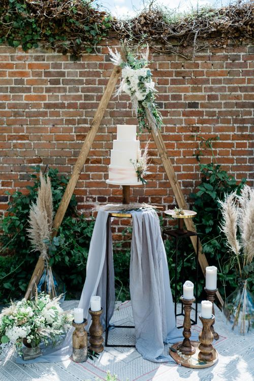 Wedding Cake Display with Wooden Triangle Backdrop, Pampas Grass and Candlesticks