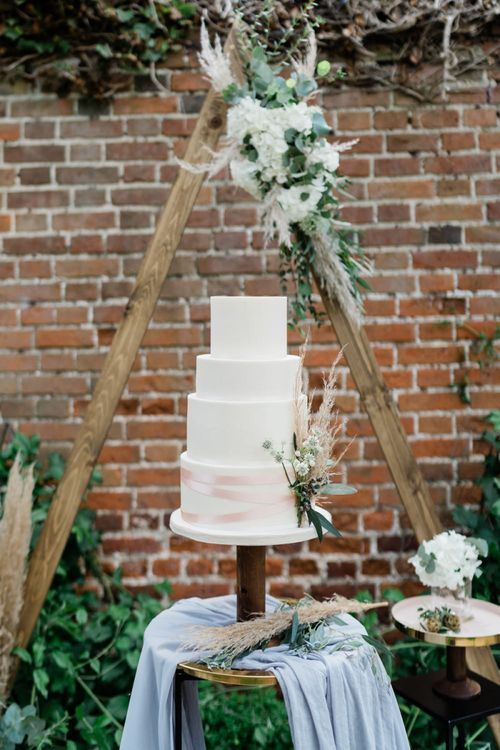 Wedding Cake Decorated with Pampas Grass Sitting on a Gold Cake Stand with Linen Table Cloth