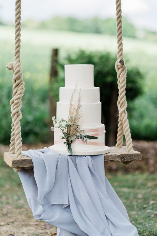 White Wedding Cake with Pampas Grass Decor on Swing Drapped in Linen