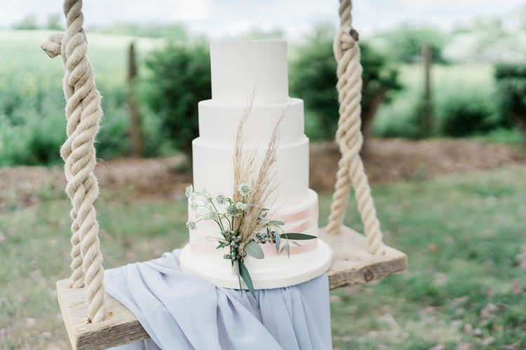 White Four Tier Wedding Cake with Pampas Grass Decor on Swing Drapped in Linen