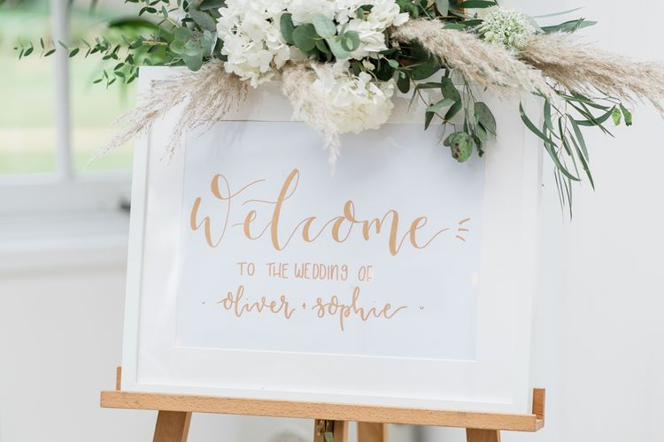 Gold Foil Wedding Welcome Sign in Frame with White Flower, Foliage and Pampas Grass Floral Arrangement