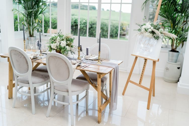 Wooden Tablescape with Grey Linen Table Runner, Gold Candlesticks and Dark Grey Taper Candles