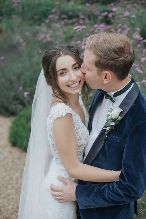 Bride with Veil and Groom in Tux with White Flower Buttonhole