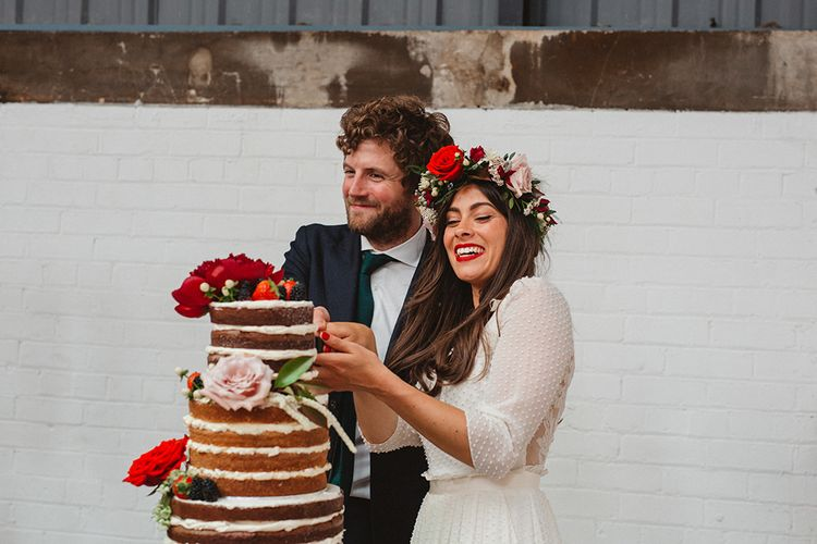 Cutting the Naked Wedding Cake | Boho Bride in Laure De Sagazan Baudelaire Bridal Gown and Flower Crown | Groom in Navy Reiss Suit | Contemporary Wedding at Industrial Venue 92 Burton Road, Sheffield | Maytree Photography