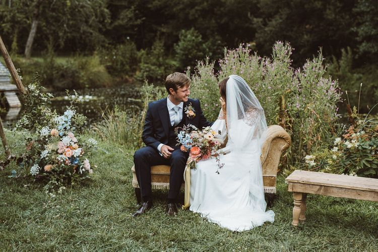 Bride in Rime Arodaky Wedding Dress and Groom is Reiss Suit Sitting on a Vintage Chaise Lounge During Outdoor Wedding Ceremony