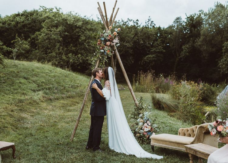 Bride in Rime Arodaky Wedding Dress and Groom is Reiss Suit at Outdoor Wedding Ceremony with Naked Tipi Altar
