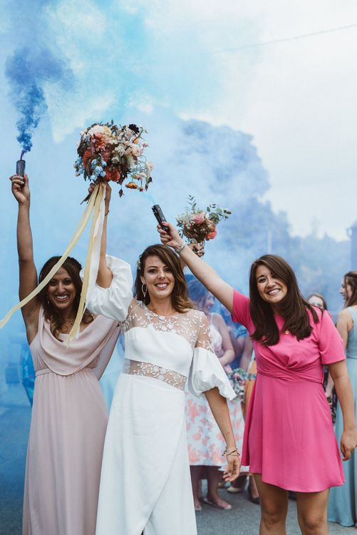 Bride in Rime Arodaky Wedding Dress and Friends Celebrating with Coloured Smoke Flares