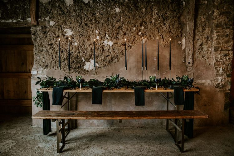 Black Taper Candles & Greenery Garland Wedding Table Decor | Forest Green and Black Dark Decadence Wedding Inspiration in a Rustic Barn Planned & Styled by Knots & Kisses with Images by Daze of Glory Photography