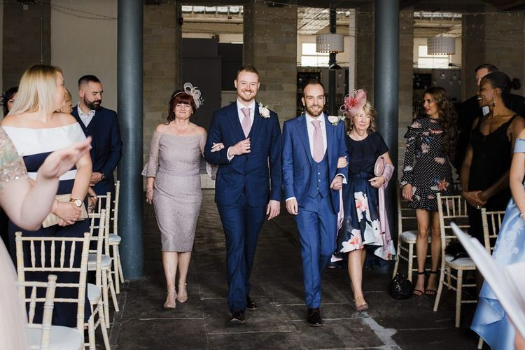 Two Grooms in Navy Blue Suits Walking Down the Aisle with Their Mums
