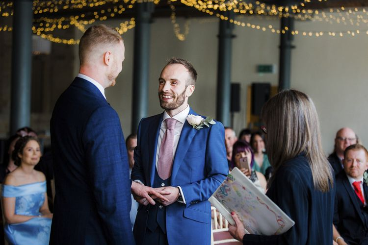 Wedding Ceremony with Two Grooms in Navy Blue Suits Exchanging Vows