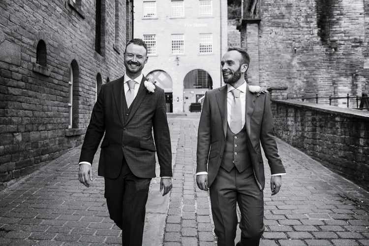 Two Groom's in Navy Suits Walking Down Cobbled Streets