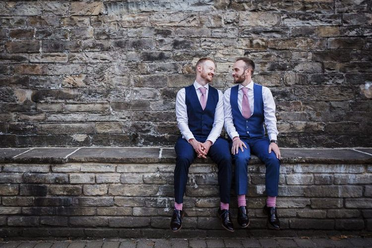 Two Grooms in Navy Suits with Pink Socks and Ties Sitting on a Wall