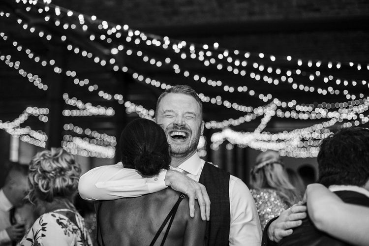 Groom Hugging Wedding Guests on the Fairy Light Covered Dance Floor