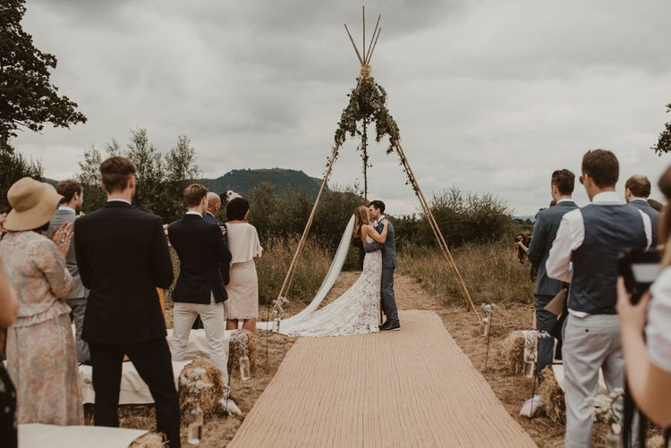 Bride in Sasha Dress by Made With Love with Crochet Finish, Fishtail Train, V-Neck and Plunging Back   Groom in Light Blue Two-Piece Suit by Hugo Boss   Blush Pink Buttonhole   Hessian Aisle   Hay Bales with White Blankets   Yurt Wedding with Outdoor Naked Tipi Ceremony, Glitter Station & Peach Rewritten Bridesmaid Dresses   Nesta Lloyd Photography