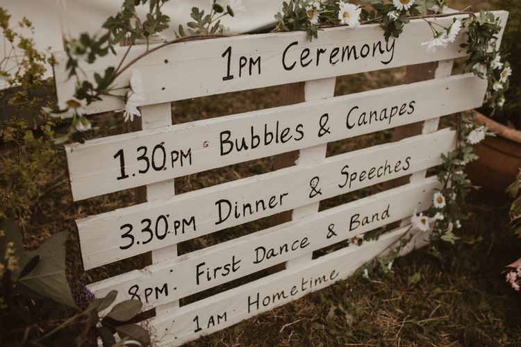 White Pallet Order of the Day Sign   Yurt Wedding with Outdoor Naked Tipi Ceremony, Glitter Station & Peach Rewritten Bridesmaid Dresses   Nesta Lloyd Photography
