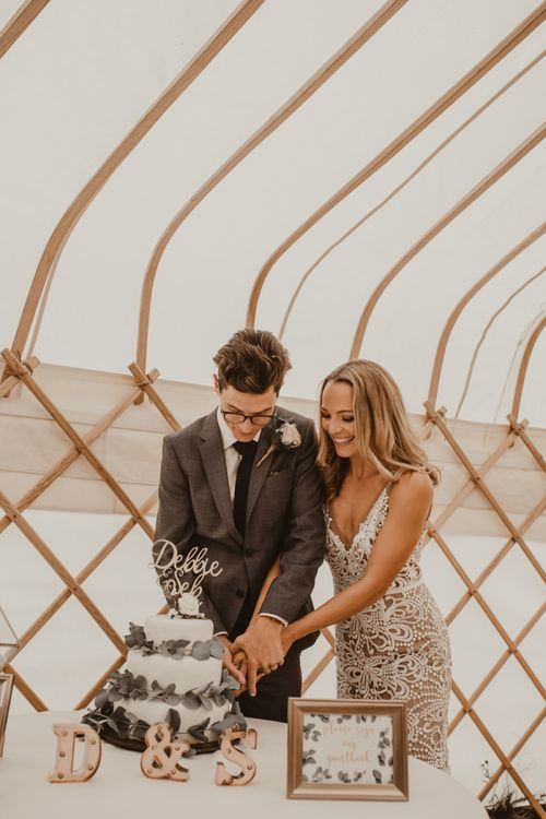 Bride in Sasha Dress by Made With Love with Crochet Finish, Fishtail Train, V-Neck and Plunging Back   Groom in Light Blue Two-Piece Suit by Hugo Boss   Blush Buttonhole   Homemade Three-Tier Iced Fruit Cake Wrapped with Eucalyptus   Laser Cut Cake Topper   Mini Letter Lights   Yurt Wedding with Outdoor Naked Tipi Ceremony, Glitter Station & Peach Rewritten Bridesmaid Dresses   Nesta Lloyd Photography