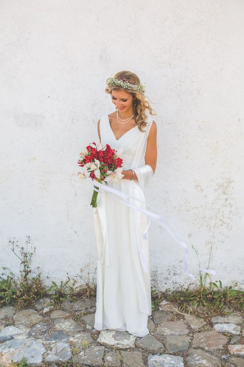 Debenhams v-neck wedding dress with floral crown and red bouquet