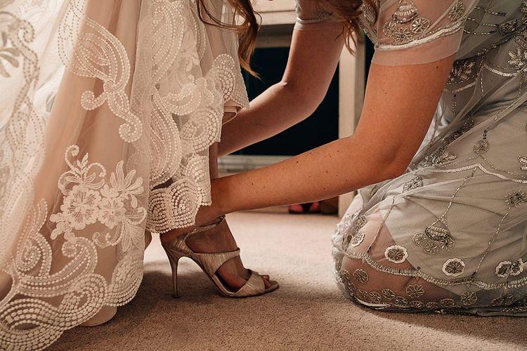 Bride putting on L.K Bennett wedding shoes