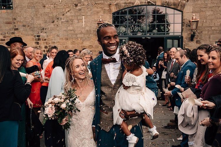 Bride, groom and daughter confetti moment by Abbie Sizer Photography