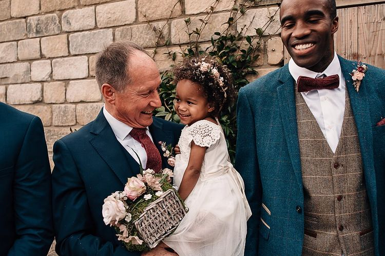 Grandfather holding his flower girl granddaughter