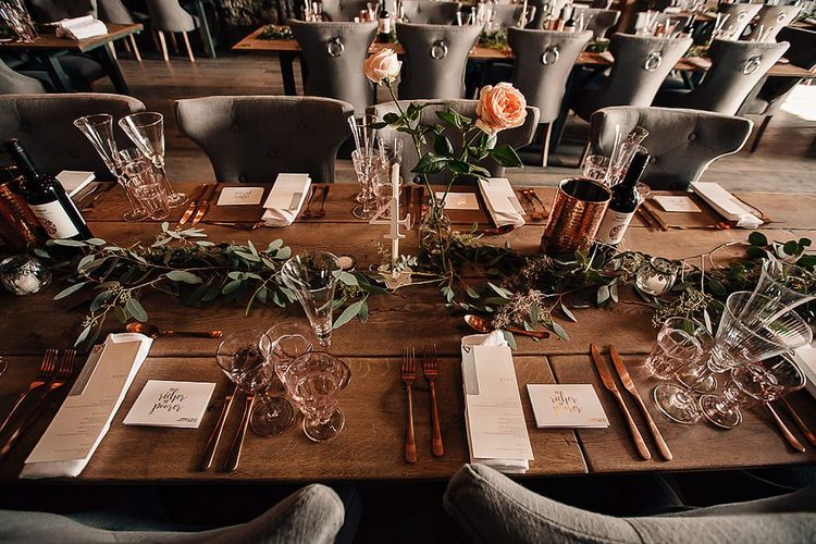Wedding table decor with copper cutlery and foliage table runners