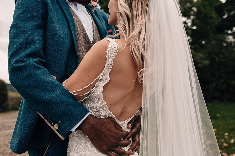 Groom embracing his bride in a lace, low back wedding dress and veil