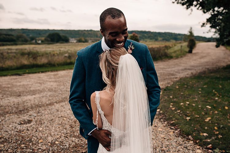 Groom in blue blazer embracing his bride in a lace wedding dress
