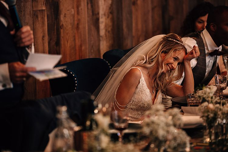 Bride laughing during wedding reception speeches