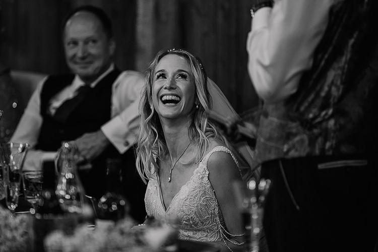 Beautiful bride smiling during grooms speech