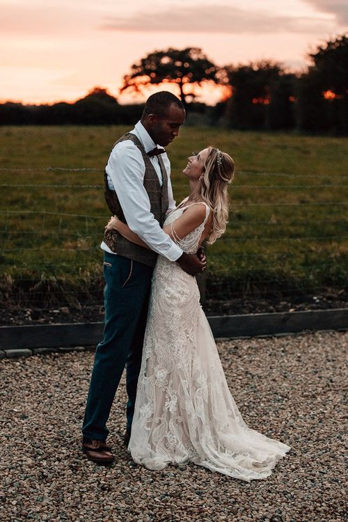 Golden hour portrait with bride in Madison James wedding Dress and groom in Marc Darcy suit