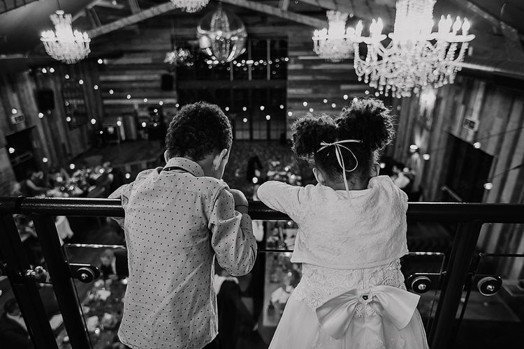 Flower girl and page boy looking over the mezzanine at Wharfedale Grange wedding venue
