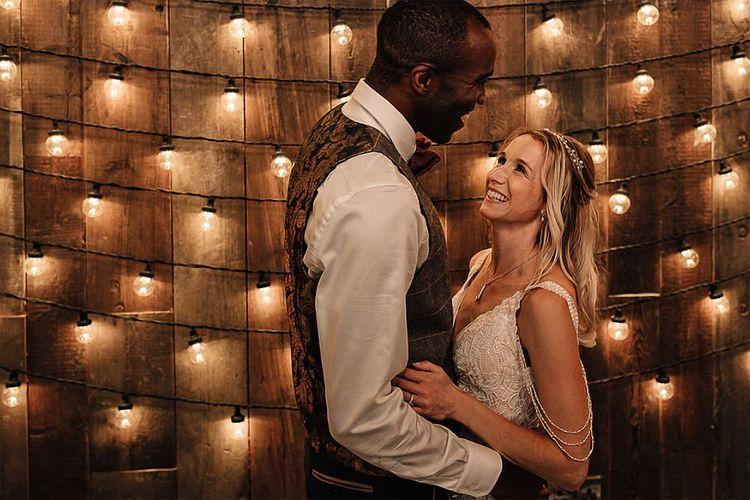 Bride and groom portrait with festoon light backdrop