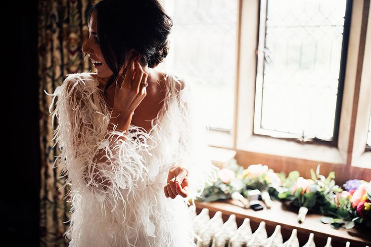 Bride in Wedding Dress with Feathers Putting Her Earrings In