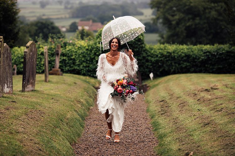 Bride in Emma Beaumont Feather Wedding Dress  Holding a Peony Bouquet and  Clear Umbrella
