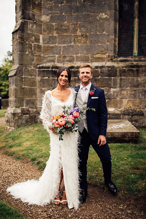 Bride in Emma Beaumont Wedding Dress and Groom in Navy Suit Outside The Church