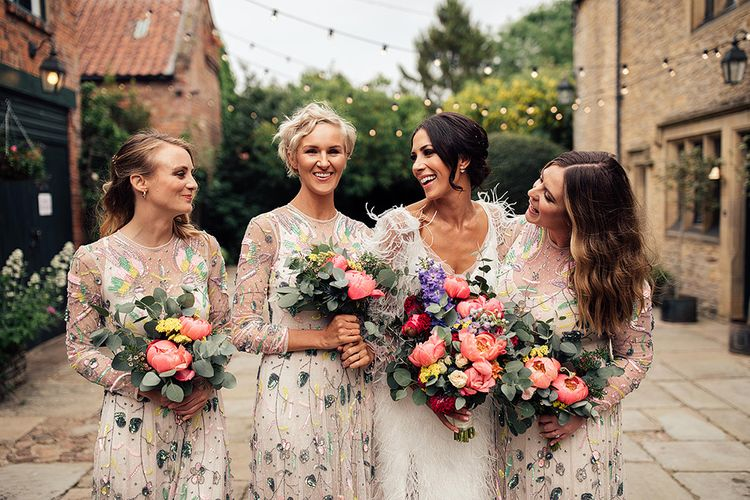 Bridal Party Portrait with Bridesmaids in Embellished Dresses Holding Bright Peony Bouquets