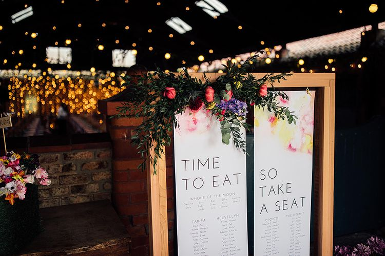 Take a Seat Wedding Sign and Bright Flowers